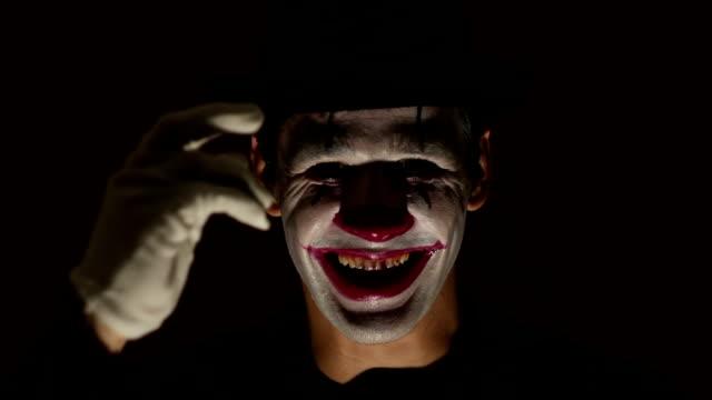 恐ろしいピエロはカメラを見て、ひどく笑います。ピエロメイクの恐ろしい男は、彼の犠牲者を歓迎することによって帽子を脱ぎ、カメラを見て笑います。ハロウィーン。 - 犯罪者点の映像素材/bロール