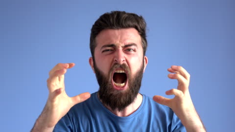 Terrified Afdult Man Screaming And Expressing Anger Emotion 4K video of terrified adult man screaming and ask for help. He is making facial expression of anger, wearing a blue sweater and the background is blue too, so the actor's face becomes more visible. He has blue eyes and brown hair. facial expression stock videos & royalty-free footage