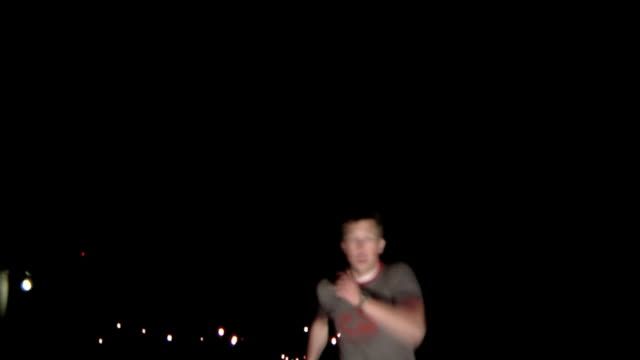 Terrified man running in street at night video