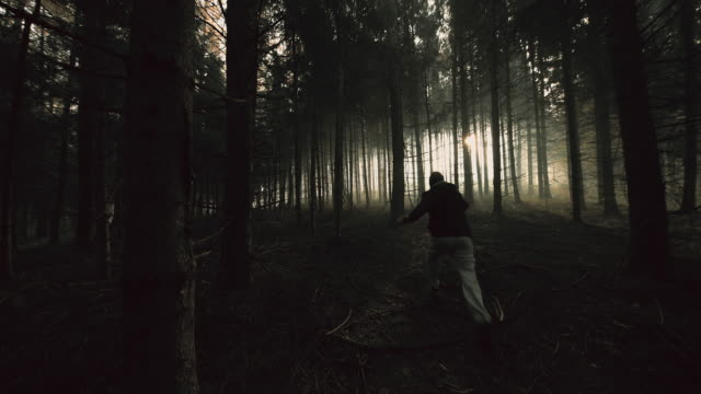 Terrified young man running in a dark forest Young man running like someone or something would chasing him in the deep dark forest. Shot includes original sound. Also available in 4K resolution. chasing stock videos & royalty-free footage