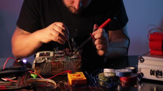 Terrorist constructing a bomb in workshop