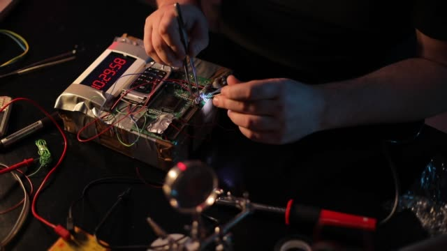 vídeos de stock e filmes b-roll de terrorist constructing a time bomb in workshop alone - bomba