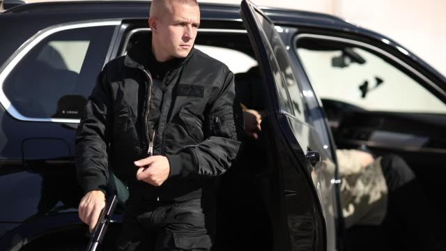 террорист выходит из машины с пистолетом в руке - элемент здания стоковые видео и кадры b-roll