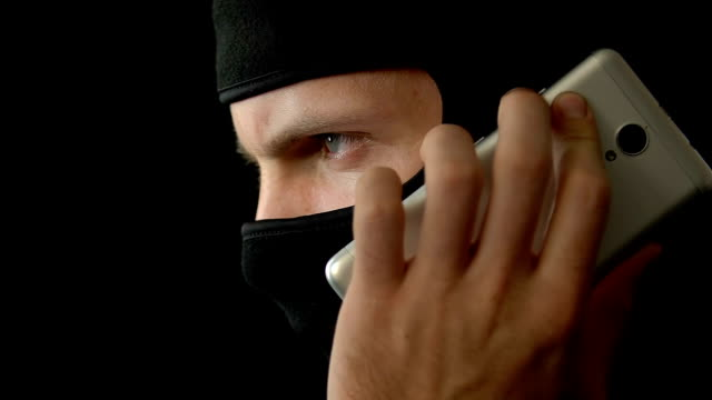 vídeos y material grabado en eventos de stock de terrorista en máscara hablando en teléfono inteligente con el compañero de crimen, secuestro, closeup - human trafficking