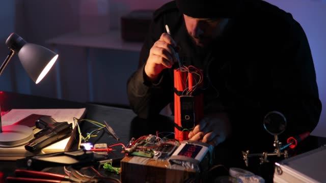 Terrorist making a dynamite bomb in workshop