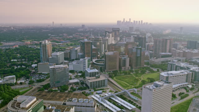 AERIAL Texas Medical Center with Downtown Houston in the background Aerial shot of the Texas Medical Center with Downtown Houston seen in the distance. Shot in Texas, USA. medical building stock videos & royalty-free footage