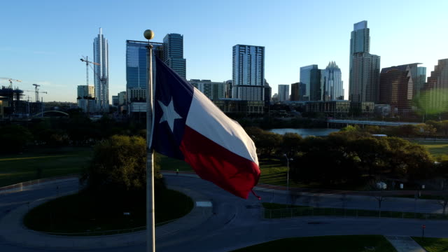 Texas State Flag Pan Right Aerial Drone view close to Flag during Sunrise over Austin Texas Skyline Cityscape of Capital Cities video