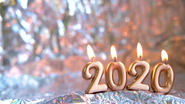 vídeos de stock e filmes b-roll de text 2020 golden candles burning. blurred silver background. copyspace. merry christmas and happy new year. selective focus.creative live greeting card. 4k footage - christmas cake