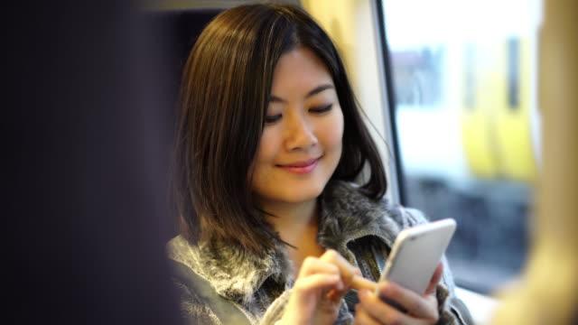 tekst wiadomości w pociągu, atrakcyjny azjatycki kobieta. - wagon kolejowy filmów i materiałów b-roll