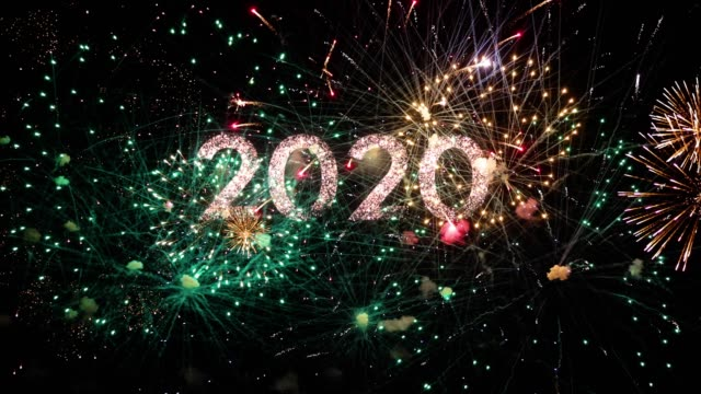 2020 text with amazing fireworks in the background. Perfect for the New Year celebration greeting with colorful fireworks, typography design - Event & Festive concept 4K 2020 text appearing in the front of wonderful fireworks. The fireworks are in wonderful colors and golden in the night sky.  This is perfect for holidays celebration and happy new year events. 2020 stock videos & royalty-free footage