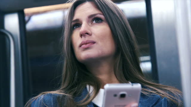 Texting in a subway (slow motion) Beautiful woman in a subway. Canon C100 Mark II. subway train stock videos & royalty-free footage