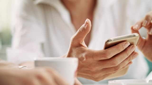 Texting messages on mobile phone Close up of woman's hands holding mobile phone on coffee break. iphone stock videos & royalty-free footage