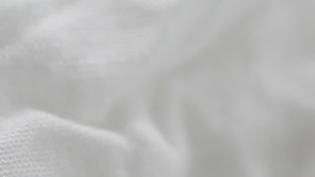 Texture of white fabric shows a soft, comfortable feel. Abstract background.