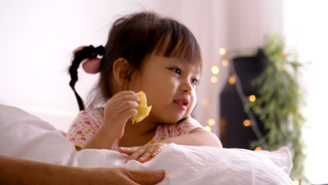 Thai baby girl is eating chip with her mother at the bedroom with positive emotion Thai baby girl is eating chip with her mother at the bedroom with positive emotion potato chip stock videos & royalty-free footage