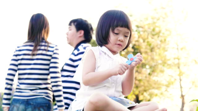 Thai baby girl is playing toy beside her parent at the garden video