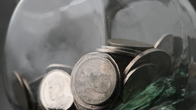 Thai baht money coins in glass bottles money saving saving video rotation 4k