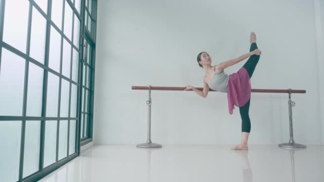 Thai Ballet dancer stretching at the barre in the classroom. She is doing her last exercises after a long session. video