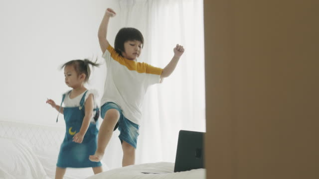 Thai boy and girl is dancing while watching computer laptop at the bedroom video