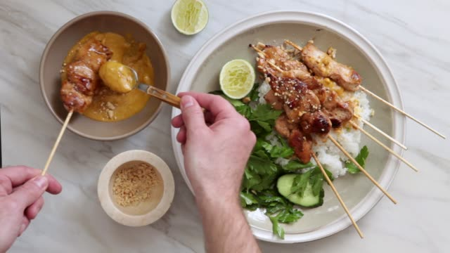 Thai Chicken Sate with Peanut Sauce Traditional Thai chicken sate with peanut sauce, rice and vegetables dipping sauce stock videos & royalty-free footage