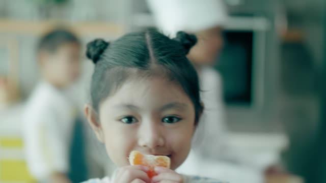 vídeos y material grabado en eventos de stock de thai linda niña bebé llevando naranja mientras mira la cámara con emoción positiva - edad humana