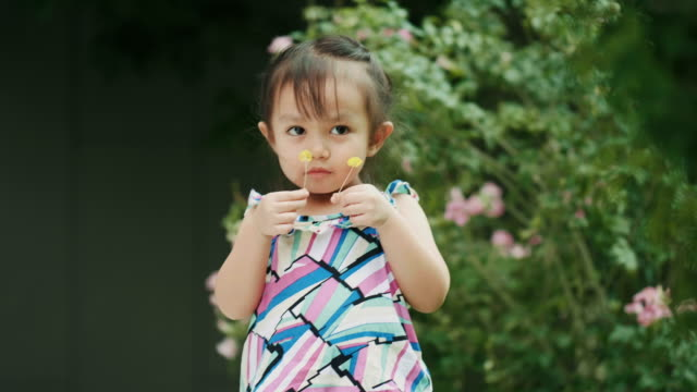 thai cute baby girl is carrying flower while smell of it at the garden - annusare video stock e b–roll