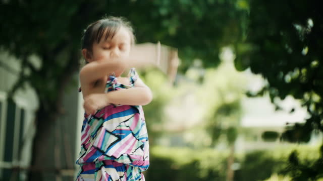 thai cute baby girl is cross one's arm with sulking and touchy at the garden - tajowie filmów i materiałów b-roll