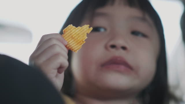 Thai cute baby girl is eating potato chip in the car while traveling on weekend with her family Thai cute baby girl is eating potato chip in the car while traveling on weekend with her family snack stock videos & royalty-free footage