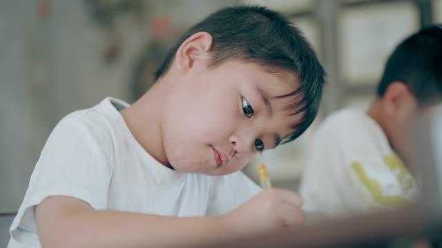 Thai cute boy doing homework beside friend at school video