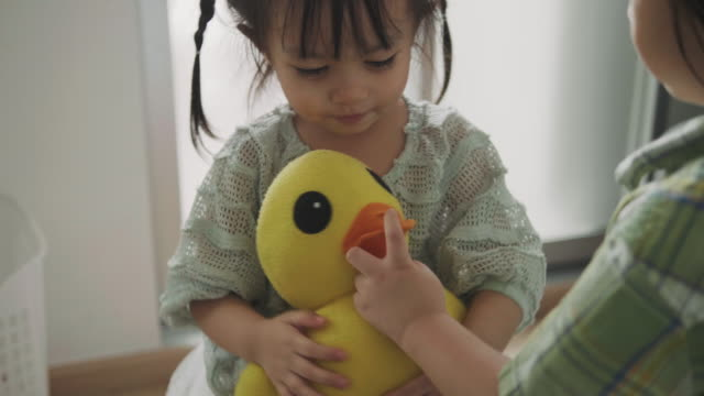 Thai cute child is embracing her ducky doll beside her brother Thai cute child is embracing her ducky doll beside her brother doll stock videos & royalty-free footage