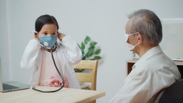 vidéos et rushes de thai filles mignonnes jouer être médecin vérifiant un patient d'hommes âgés utilisant le stéthoscope à la maison - enfant masque