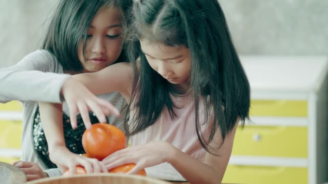 Thai cute girls trying to measure the orange fruit before making some smoothie
