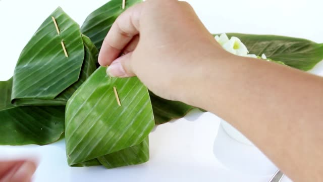 Thai dessert: Glutinous Rice with Dried Fish Topping with wrapped in banana leaf on white background. video