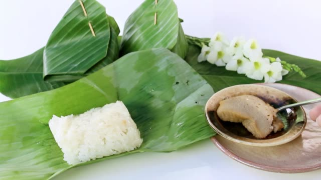 Thai dessert: Sticky rice and steamed custard with wrapped in banana leaf on white background. video
