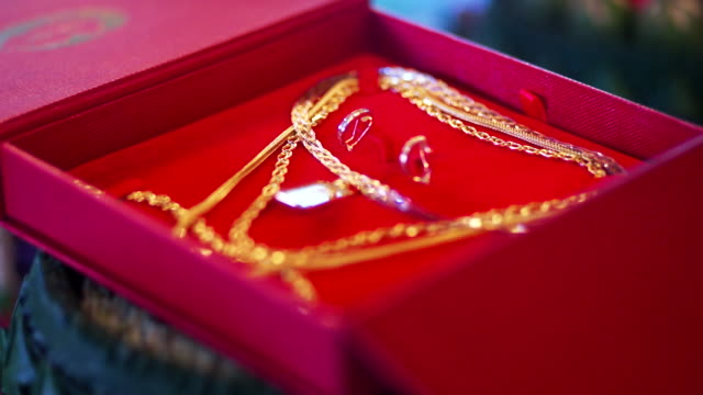 Thai dowry with gold necklaces on a red box for the bride during a part of the Thai engagement or a wedding ceremony.
