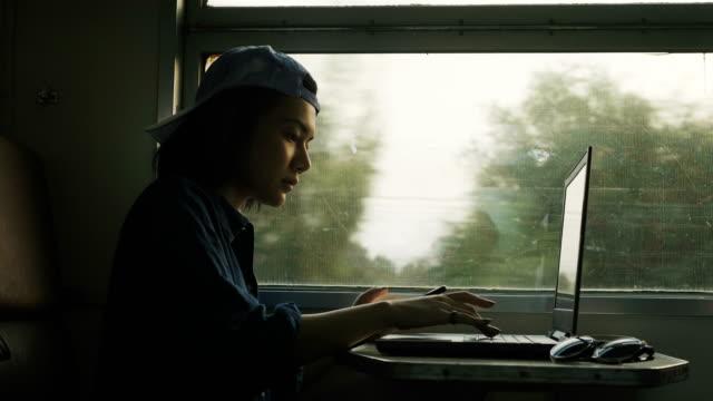 移動しながら電車の中のコンピューターのノート パソコンを扱うタイ フリーランサー - 列車点の映像素材/bロール