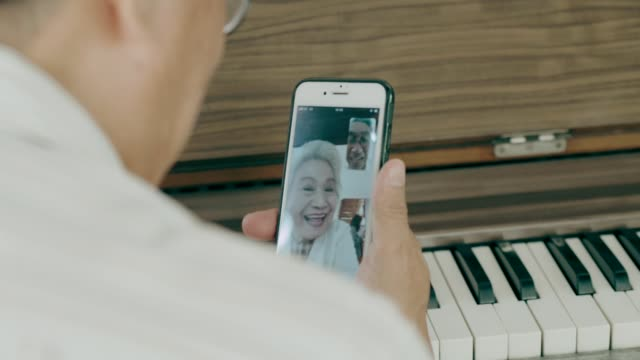 Thai grandfather talking to grandmother while using smart phone in her house with love and missing him