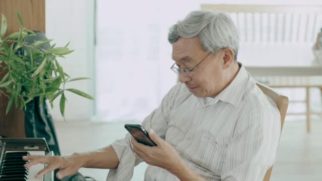 Thai grandfather talking to her wife while using smart phone in her house with love and missing him video