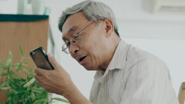 vídeos de stock e filmes b-roll de thai grandfather talking to her wife while using smart phone in her house with love and missing him - alzheimer