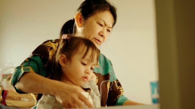 thailändska mormor är undervisning läxor till sin systerdotter - konst och konshantverk bildbanksvideor och videomaterial från bakom kulisserna