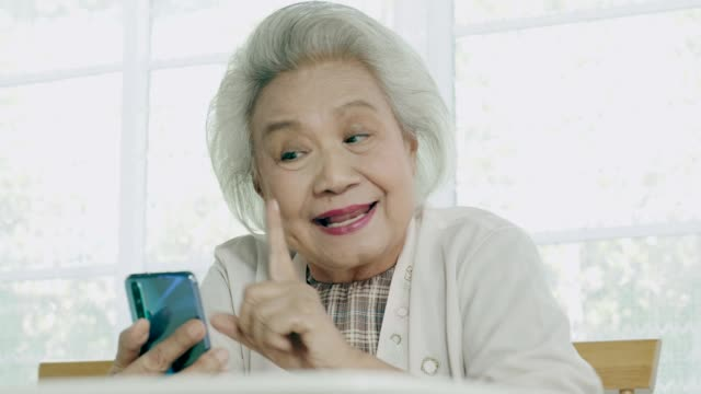 Thai grandmother talking to her husband while using smart phone in her house with love and missing him video