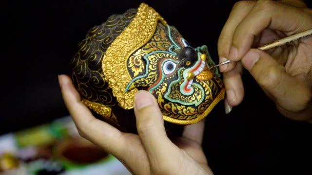 vídeos de stock, filmes e b-roll de 4k khon tailandês máscara lembrancinha pintura de arte interior. - cultura tailandesa