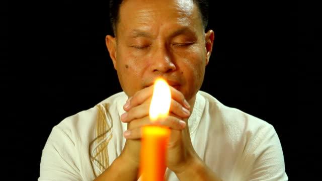 stockvideo's en b-roll-footage met thaise man bidden met zwarte achtergrond - heilig geschrift