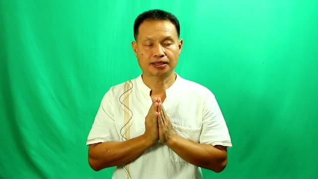 stockvideo's en b-roll-footage met thaise man bidden met groene achtergrond - heilig geschrift