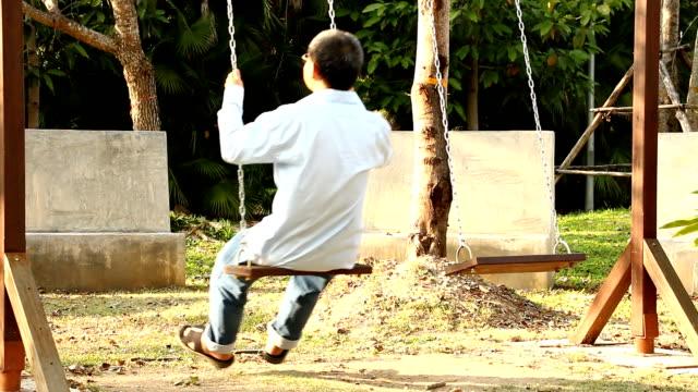 stockvideo's en b-roll-footage met thaise man swingen in de tuin - tarzan