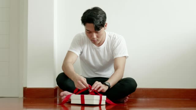 Thai man trying to make gift box for surprise to girlfriend for Valentine and birthday celebration