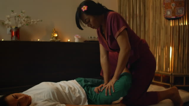 vídeos de stock e filmes b-roll de thai massage salon. asian woman in traditional clothes doing therapeutic relaxing massage, caucasian woman. professional traditional massage. alternative medicine - cultura tailandesa