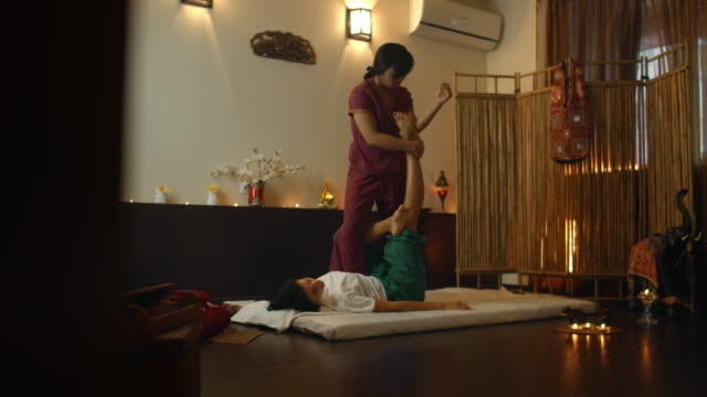 thai massage salon. asian woman in traditional clothes doing therapeutic relaxing massage, caucasian woman. professional traditional massage. alternative medicine - cultura tailandese video stock e b–roll