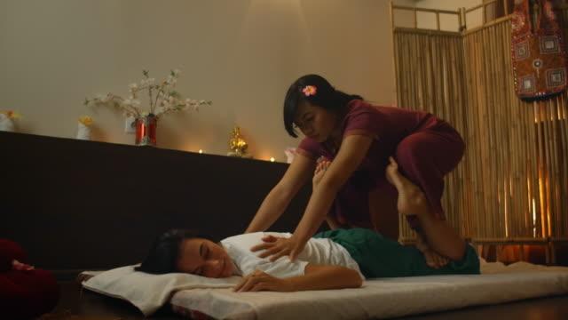 vídeos de stock, filmes e b-roll de salão de massagem tailandês. mulher asiática na roupa tradicional que faz a massagem de relaxamento terapêutica, mulher caucasiana. massagem tradicional profissional. medicina alternativa - cultura tailandesa