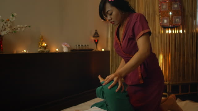 thai massage. the asian woman rubbed by traditional chiropractor on his back with the hands to relieve tension or pain. - cultura tailandese video stock e b–roll