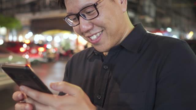 thai kontorsman i glasögon med smartphone med gatunatten bokeh bakgrund - endast en man i 30 årsåldern bildbanksvideor och videomaterial från bakom kulisserna